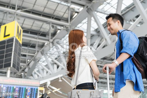 842907838 istock photo Asian couple student college traveler standing with suitcases at the airport. Lover travel and transportation at airport terminal. 823207520