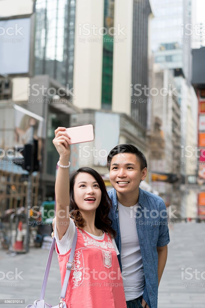 Asian couple taking a selfie on the street royalty-free stock photo