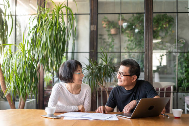 Asian couple talking about buying a new house Asian couple talking about buying a new house. face to face stock pictures, royalty-free photos & images