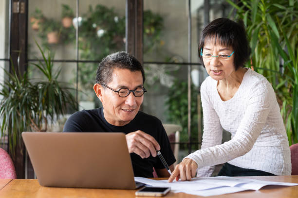 Asian couple talking about the design of their new house stock photo