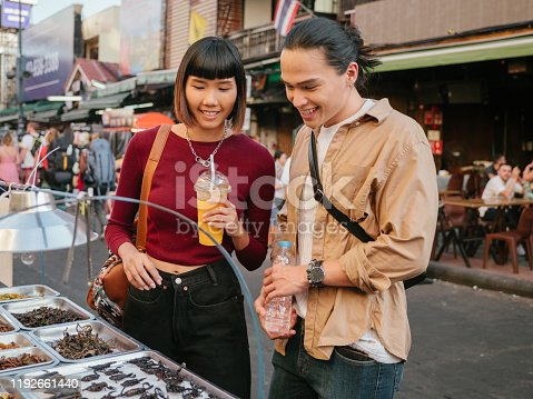 Young asian man tourist choosing fired insects in street food with his girlfriend at Khao San Road, Bangkok, Thailand.