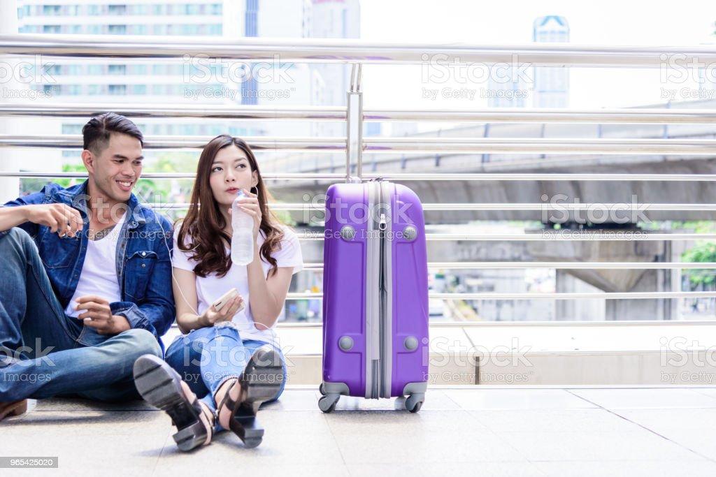 亞洲情侶遊客有飲水和大紫色袋一起。 - 免版稅人圖庫照片