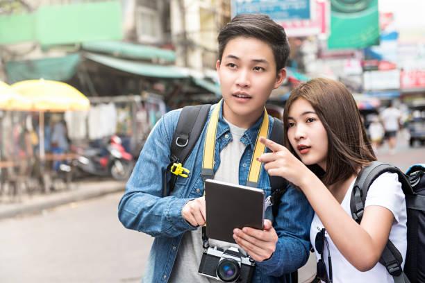 turismo de pareja asiática utilizando tablet para encontrar ubicación al viajar en tailandia - regreso a clases fotografías e imágenes de stock