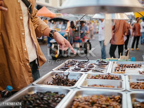 Young couple tourists buy fired insects in a street food marketplace in Bangkok, at Khao San Road