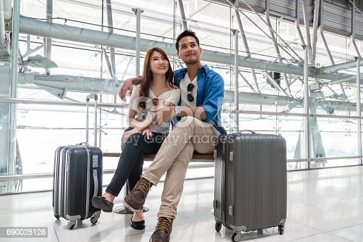 842907838 istock photo Asian couple traveler using smartphone and listening the song when waiting the airplane arrive with luggage at the airport. Lover travel and transportation with technology concept. 690025126