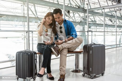 istock Asian couple traveler using smartphone and listening the song when waiting the airplane arrive with luggage at the airport. Lover travel and transportation with technology concept. 909590222