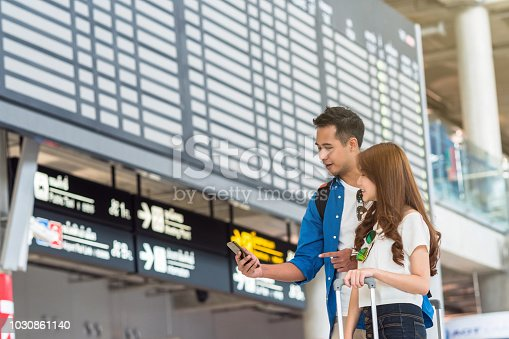 istock Asian couple traveler using the smart mobile phone for check-in at the flight information screen in moddern an airport, travel and transportation with technology concept. 1030861140