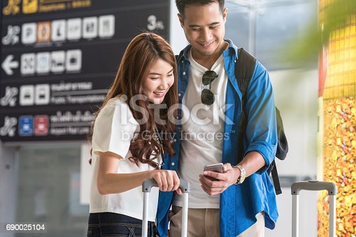 istock Asian couple traveler using the smart mobile phone for check-in at the flight information screen in moddern an airport, travel and transportation with technology concept. 690025104