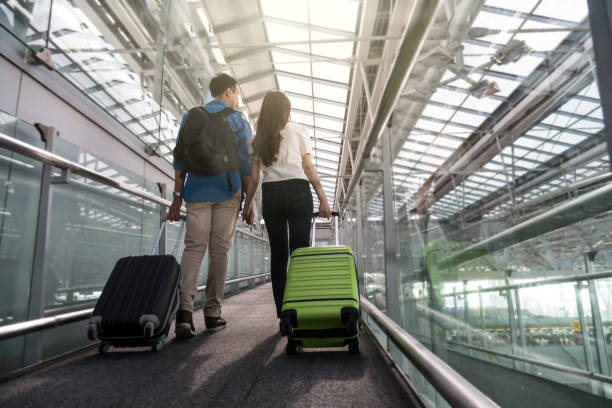 asian couple traveler with suitcases at the airport. lover travel and transportation with technology concept. - aids healthcare foundation foto e immagini stock