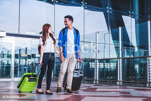 istock Asian couple traveler with suitcases at the airport. Lover travel and transportation with technology concept. 873454606
