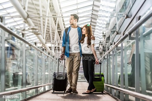 istock Asian couple traveler with suitcases at the airport. Lover travel and transportation with technology concept. 873572280