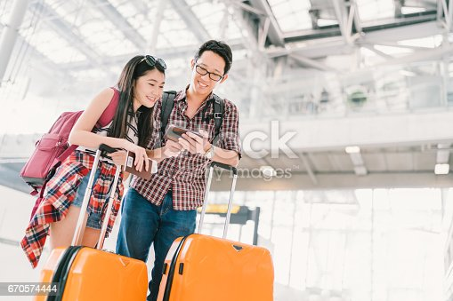 istock Asian couple travelers using smartphone checking flight or online check-in at airport, with passport and luggage. Air travel or mobile phone technology concept 670574444
