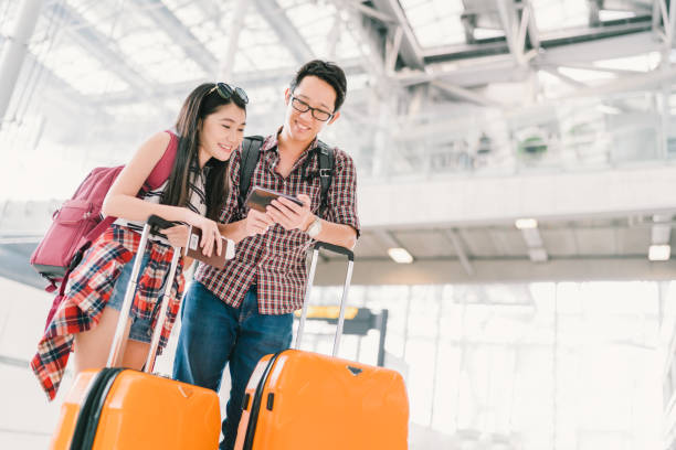Asian couple travelers using smartphone checking flight or online check-in at airport, with passport and luggage. Air travel or mobile phone technology concept stock photo