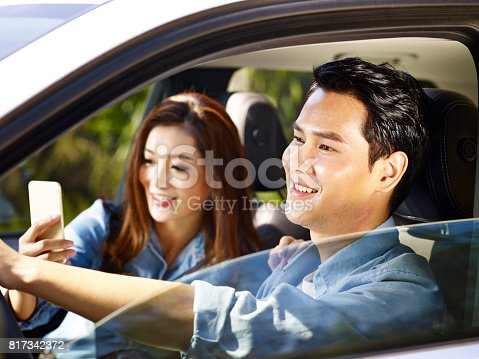 817334706 istock photo asian couple traveling by car 817342372