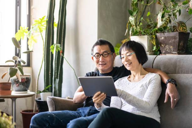 Asian couple using a digital tablet on sofa stock photo