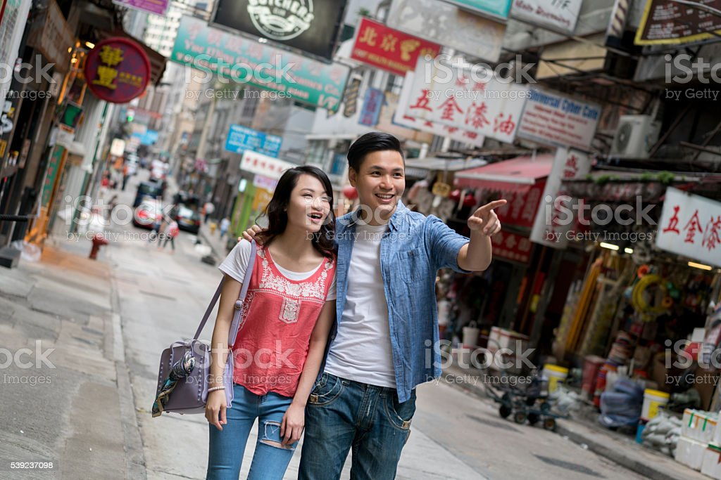 Asian couple walking in the streets of Hong Kong royalty-free stock photo