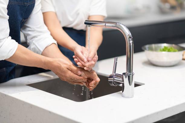Pareja asiática lavarse las manos con jabón de espuma antes de cocinar en casa. - foto de stock