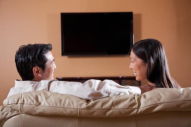 asiatische paar vor dem fernseher - tv wand profile stock-fotos und bilder