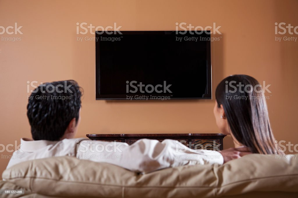 Rear view of Asian couple watching TV. Focus on flat screen.