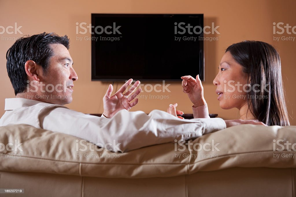 Asian couple watching TV, talking stock photo