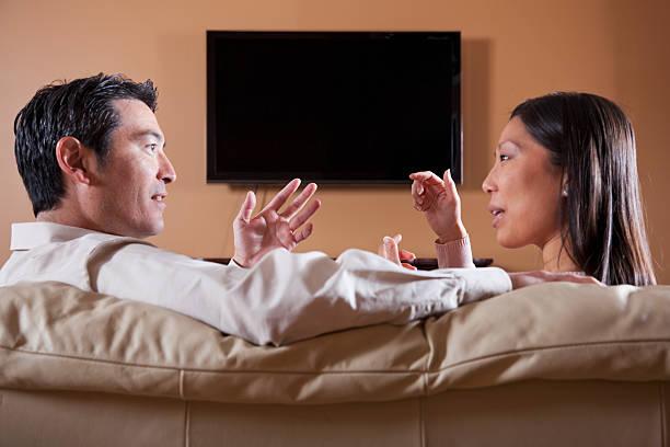 asiatische paar beobachten fernseher, reden - tv wand profile stock-fotos und bilder