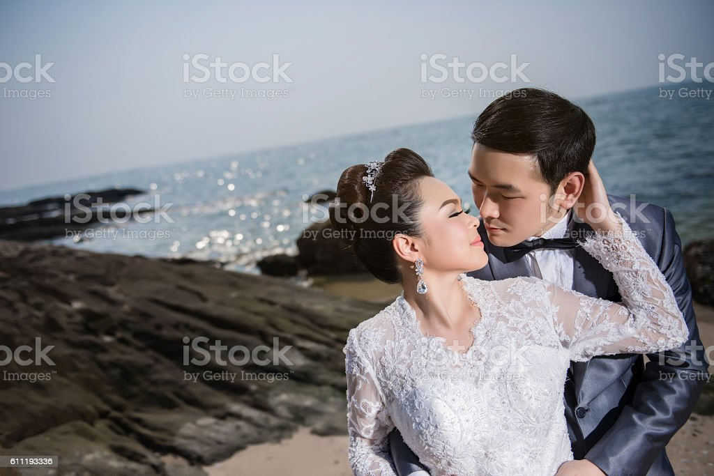 Asian couple wearing wedding dress and suit for beach wedding stock photo