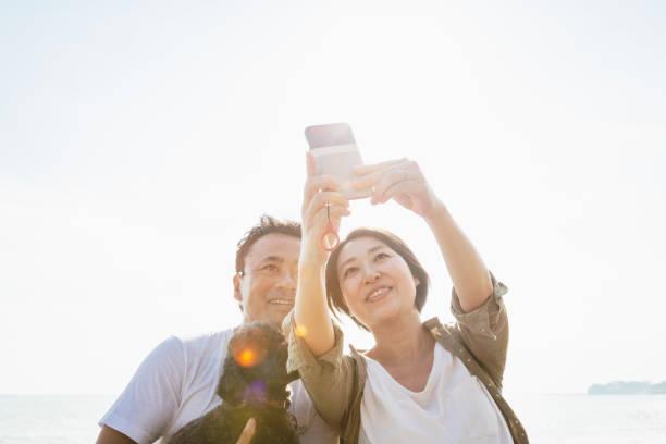 Pares asiáticos com o cão que toma o selfie na praia - foto de acervo