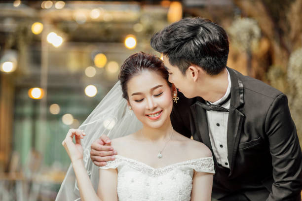 Asian couples are whispering and tell some sweet wording with smiling faces. stock photo