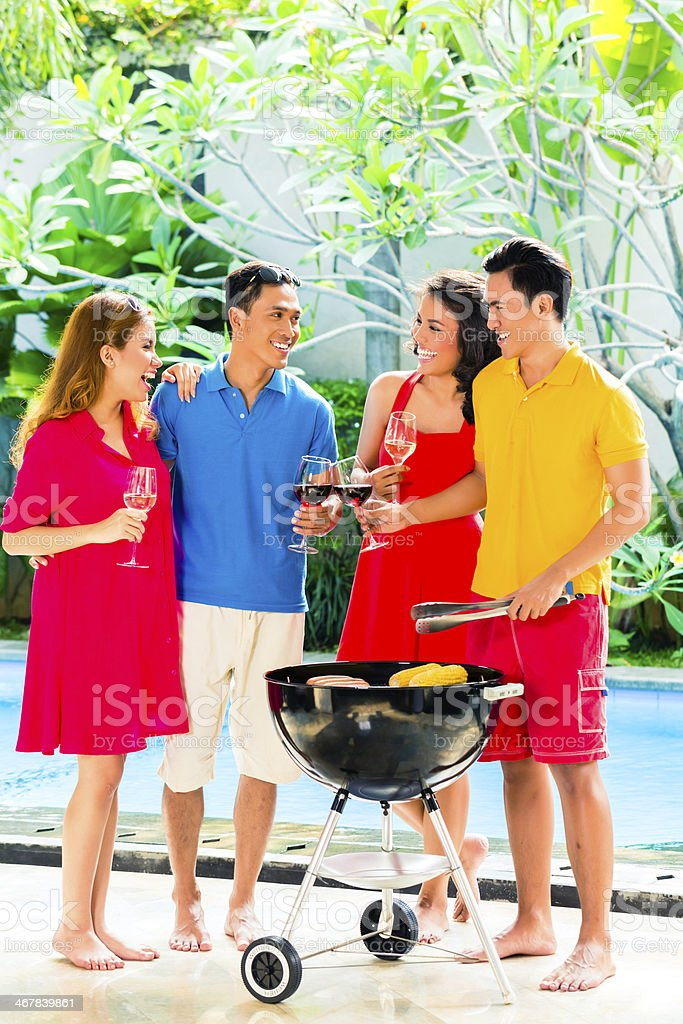 Asian couples enjoying barbecue outside while drinking wine stock photo