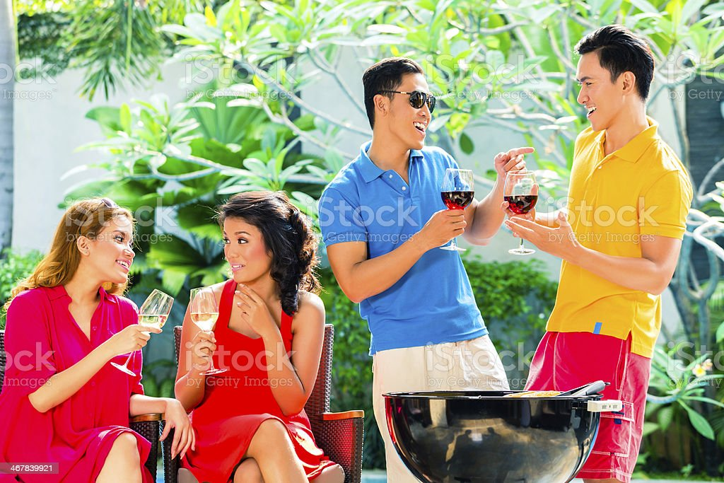 Asian couples having barbecue and drinking wine stock photo