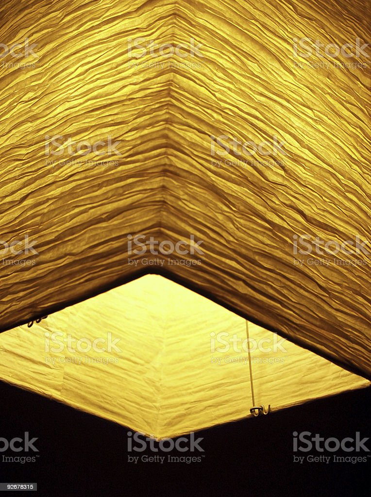 Asian Crinkly Paper Lantern with Golden Light in Dark stock photo