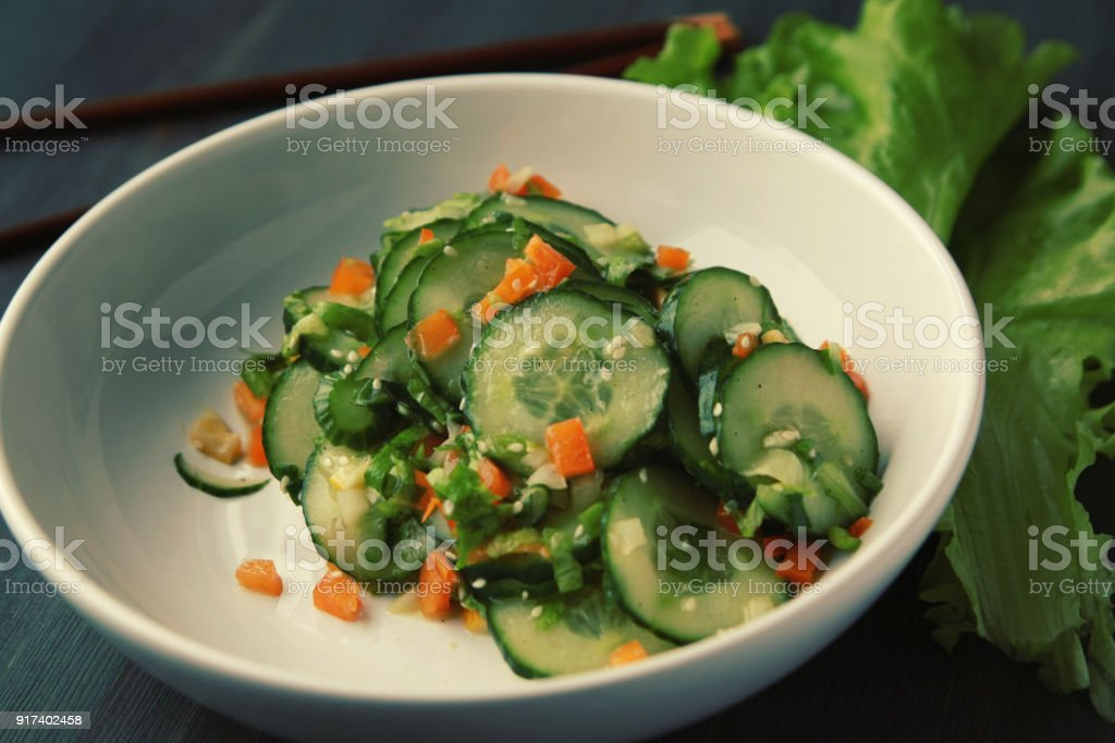 Asian cucumber salad on the white plate. Close up. - Stock image .