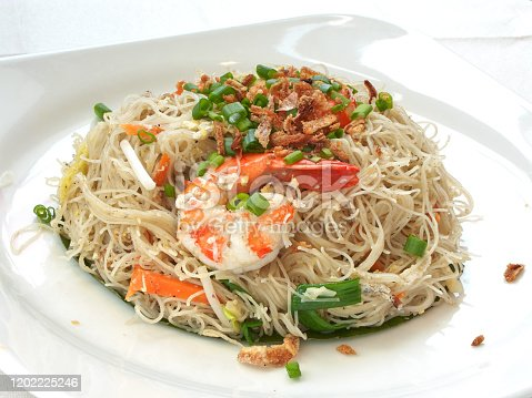 Asian cuisine - King Prawn Rice Vermicelli Stir-fry, with fritters, spring onions, eggs, carrots, and bean sprouts.