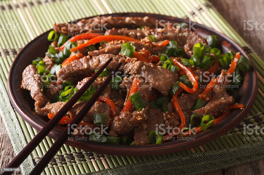 Asian cuisine: slices of beef fried with sesame and carrot stock photo