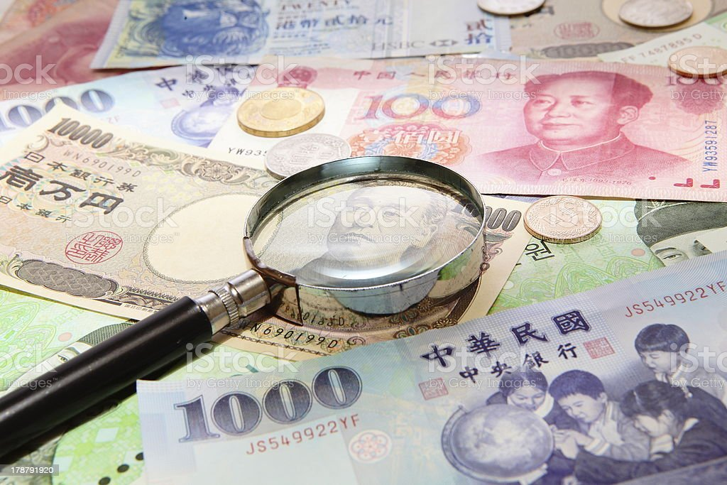 asian currency and magnifying glass stock photo