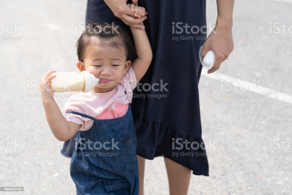 Asian cute baby eating milk in bottle. zbiór zdjęć royalty-free