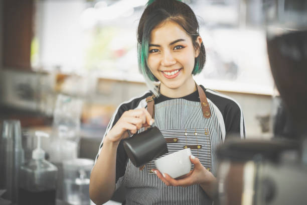 Asian cute barista woman making coffee in the coffee shop stock photo