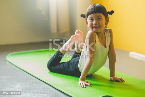 Image of Asian cute girl Practicing On Yoga Mat at living room.