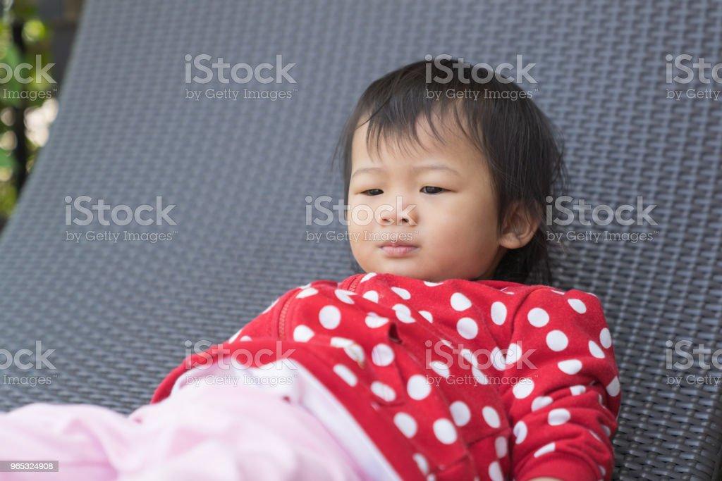 Asian cute girl kid is boring on modern sofa. zbiór zdjęć royalty-free