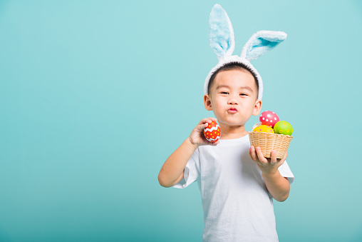 Asian cute little child boy smile beaming wearing bunny ears and a white T-shirt, standing to hold a basket with full Easter eggs. And other hand holds an easter egg