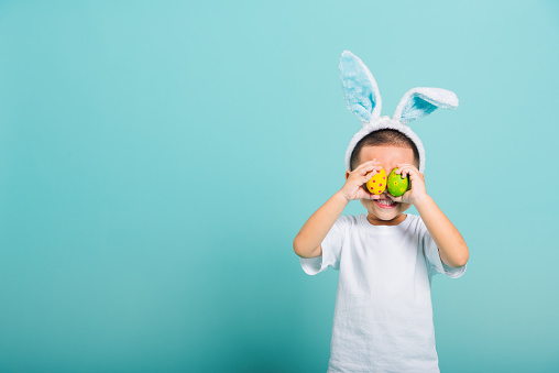 Asian cute little child boy smile beaming wearing bunny ears and a white T-shirt, standing to holds colored easter eggs instead of eyes