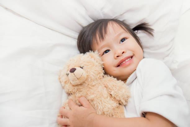 mignon petit enfant asiat étreindre les ours en peluche dans le lit - doudou photos et images de collection