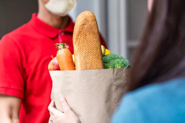 asiático saem com máscara facial em saco vermelho de manipulação de alimentos, frutas, legumes para mulheres clientes na frente da casa. carteiro e serviço de entrega expressa de mercearia durante o covid19. - costumer - fotografias e filmes do acervo