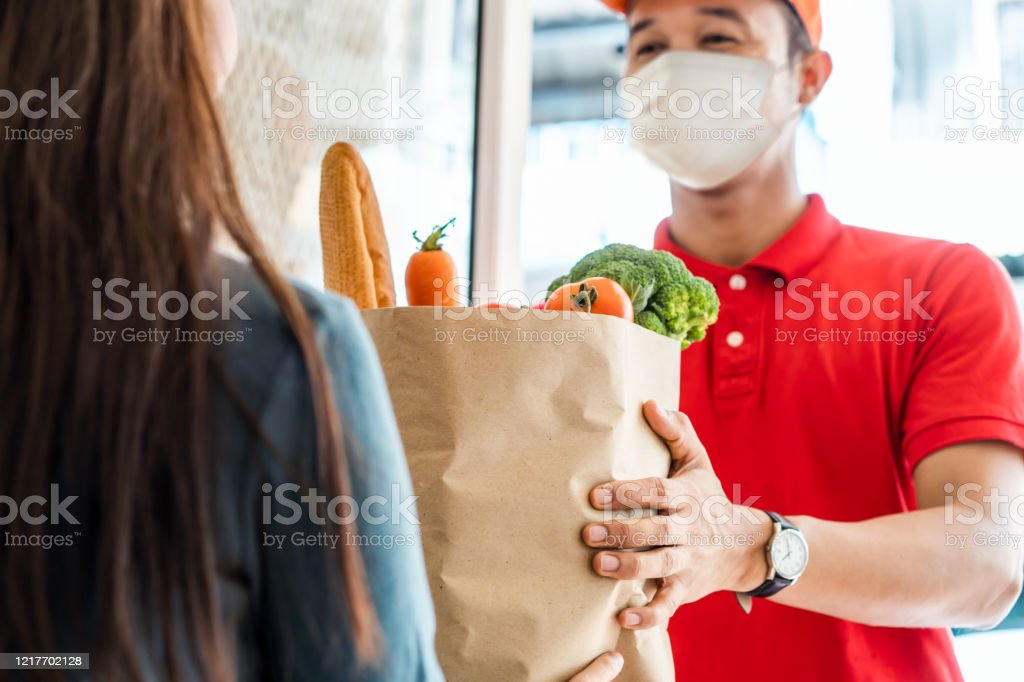 Asiático entregar hombre usando máscara facial en rojo uniforme manipulación bolsa de comida, fruta, verduras dar a la mujer cliente en frente de la casa. Servicio de entrega de correos y comida exprés durante covid19. - Foto de stock de Adulto libre de derechos