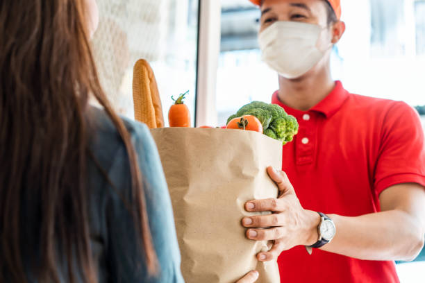 asian deliver man wearing face mask in red uniform handling bag of food, fruit, vegetable give to female costumer in front of the house. postman and express grocery delivery service during covid19. - servizi essenziali foto e immagini stock