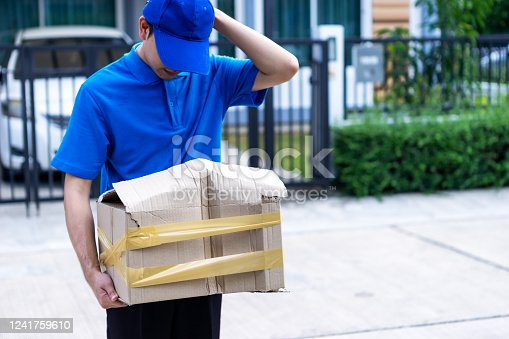 800345184 istock photo Asian delivery man in blue uniform he emotional falling courier courier showing damaged box, cheap parcel delivery, poor shipment quality. 1241759610