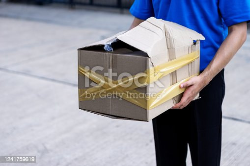 800345184 istock photo Asian delivery man in blue uniform he emotional falling courier courier showing damaged box, cheap parcel delivery, poor shipment quality. 1241759619