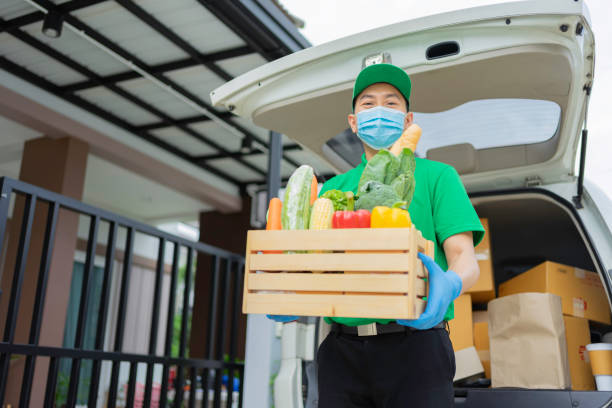 Asian delivery man in green uniform, standing with arms crossed and smiling, is delivering food to customers ordering online at home, stock photo