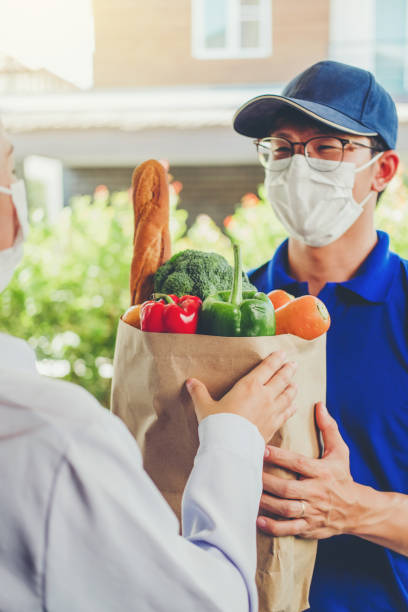 Asian delivery man wearing face mask hand giving bag of food, fruit, vegetable delivery to female customer grocery delivery service during covid19. stock photo