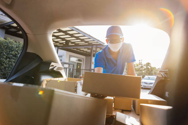 asian delivery man wearing mask picking up the package on front receiver shipping deliver cargo social distancing, many parcel in trunk hatchback car while the virus is spreading at sunset. - gmail imagens e fotografias de stock